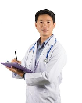 Asiatischer männlicher doktor ist nett und trägt einen weißen grundmantel. notizen machen.