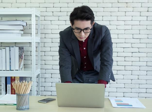 Asiatischer männlicher firmenangestellter oder geschäftsmann, der am schreibtisch im büro sitzt