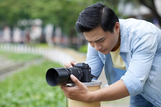 Asiatischer männlicher fotograf, der kamera im städtischen park gründet