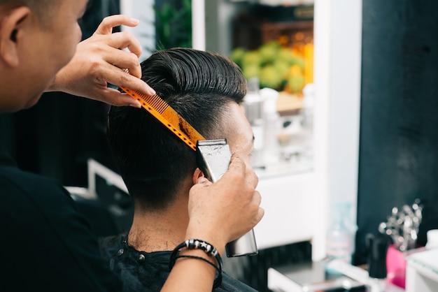 Asiatischer männlicher friseur, der kamm und trimmer zum kopf des kunden hält