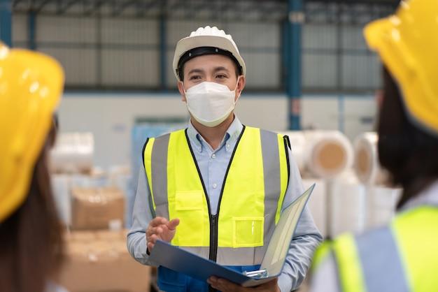 Asiatischer männlicher ingenieur, der helmsicherheit und maske trägt, erklärt den plan zur teamarbeit in der lagerfabrik