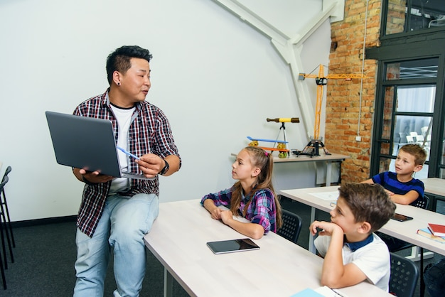 Asiatischer männlicher lehrer sitzt mit laptop in händen auf schreibtisch und erklärt unterricht für sechs grundschüler. schulkinder sitzen an schreibtischen und hören ihrem dozenten zu.