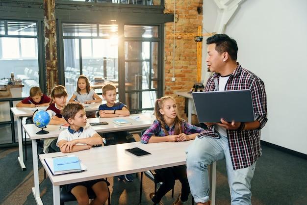 Asiatischer männlicher lehrer sitzt mit laptop in händen auf schreibtisch und erklärt unterricht für sechs grundschüler.
