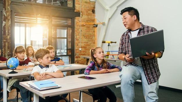 Asiatischer männlicher lehrer sitzt mit laptop in händen auf schreibtisch und erklärt unterricht für sechs grundschüler