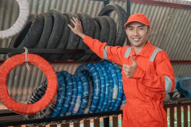 Asiatischer männlicher mechaniker in einem wearpack mit einem daumen hoch stehen mit reifenständer