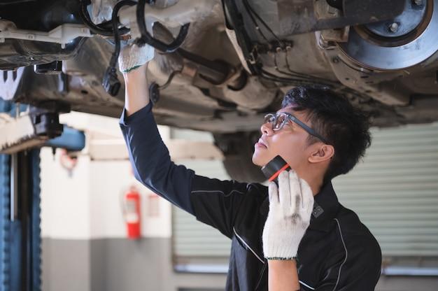 Asiatischer männlicher mechanischer griff und glänzende taschenlampe, zum des autos unter fahrgestellen zu überprüfen