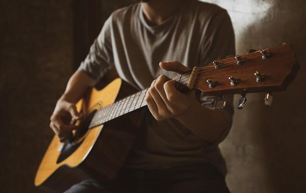 Asiatischer männlicher musiker, der akustikgitarrensolo-fingerart-sammeln in der raumecke spielt.