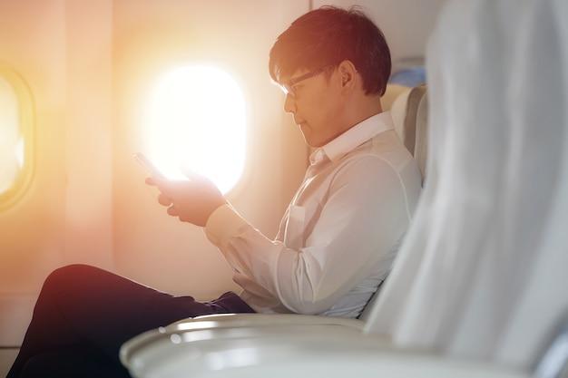 Asiatischer männlicher passagier des flugzeugs liest nachrichten aus netzwerken über smartphone und wlan an bord