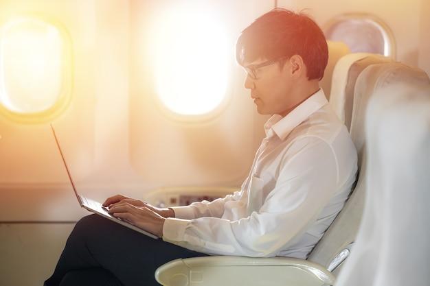 Asiatischer männlicher passagier im flugzeug liest nachrichten aus netzwerken über notebook-laptop und wlan an bord