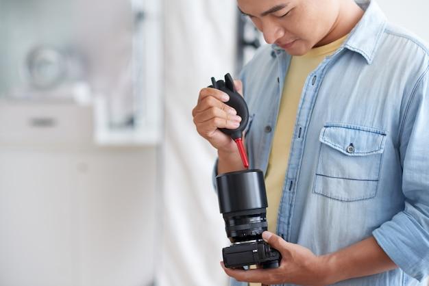 Asiatischer männlicher phograph, der kameraobjektiv mit luftgebläse säubert