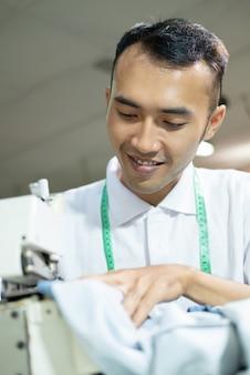 Asiatischer männlicher schneider näht akribisch mit einer nähmaschine in einer bekleidungsfabrik