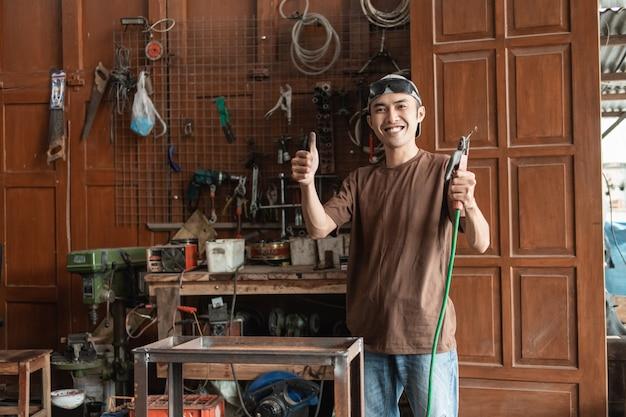 Asiatischer männlicher schweißer lächelt mit einem daumen nach oben, während er einen elektrischen schweißer im hintergrund der schweißwerkstatt hält