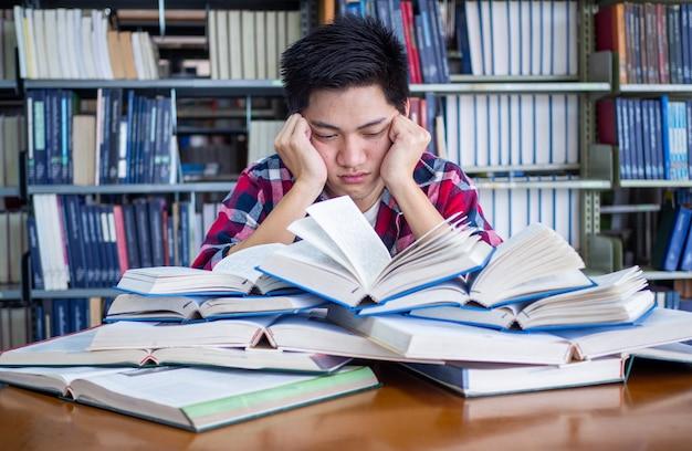 Asiatischer männlicher student ist müde und gestresst in der bibliothek
