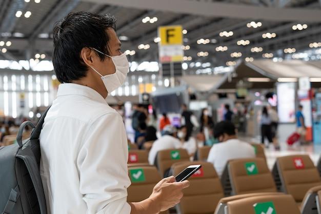 Asiatischer männlicher tourist, der eine maske trägt, wartet auf ein flugzeug, steht in der abflughalle des flughafens. männliche passagiere, die während des ausbruchs des coronavirus mit dem flugzeug reisen.