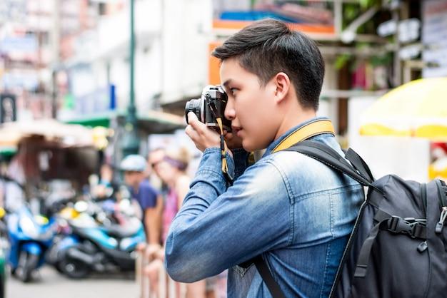 Asiatischer männlicher touristischer fotograf, der foto an straße khao san in bangkok-stadt macht