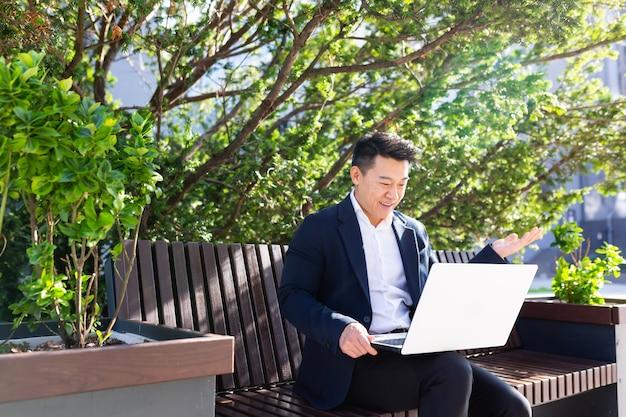 Asiatischer männlicher unternehmer-freiberufler, der draußen im stadtpark sitzt, eine bank, die online einen videoanruf mit laptop spricht geschäftsmann büroangestellter, der auf urbanem straßenhintergrund arbeitet geschäftsmann kommuniziert