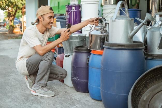 Asiatischer männlicher verkäufer hockt mit telefonkamera, wenn er einen wasserkocher vor dem haushaltsgerätegeschäft fotografiert