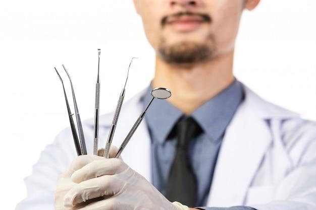Asiatischer männlicher zahnarzt mit werkzeugen auf weiß