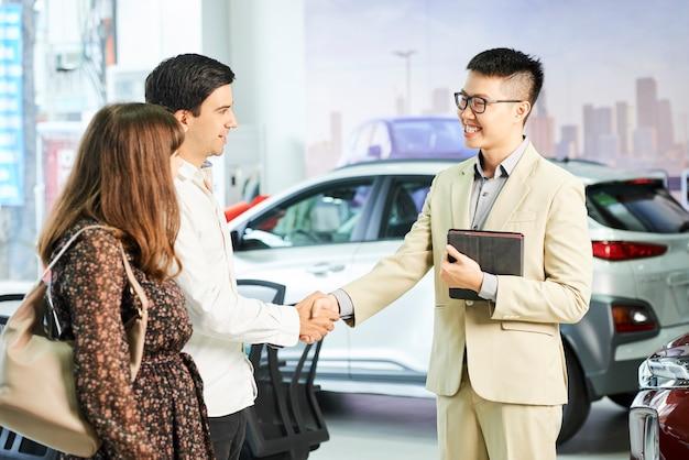 Asiatischer manager in brillen, die junges paar mit handschlag im autoausstellungsraum lächeln und begrüßen