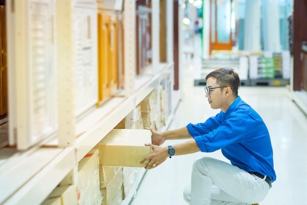 Asiatischer managermann, der inventur von produkten in der pappschachtel auf regalen im lager unter verwendung der digitalen tablette und des stiftes tut. männlicher berufsassistent, der vorrat an fabrik überprüft. inventurzählung.
