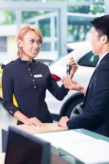 Asiatischer mann an der automiete, die schlüssel empfängt