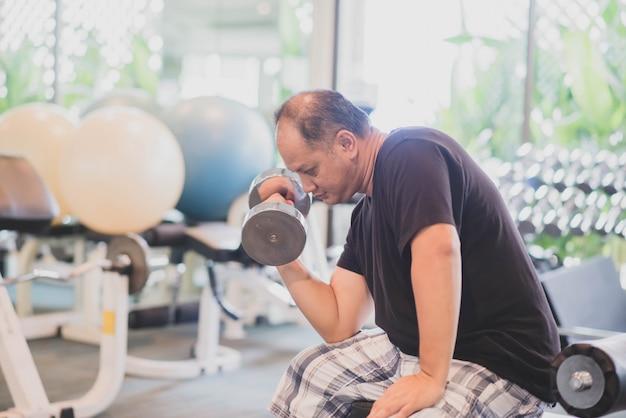 Asiatischer mann arbeiten übung am turnhallengewichtsverlust aus