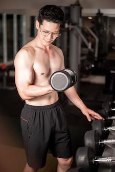 Asiatischer mann arbeitet in der eignungsturnhalle aus