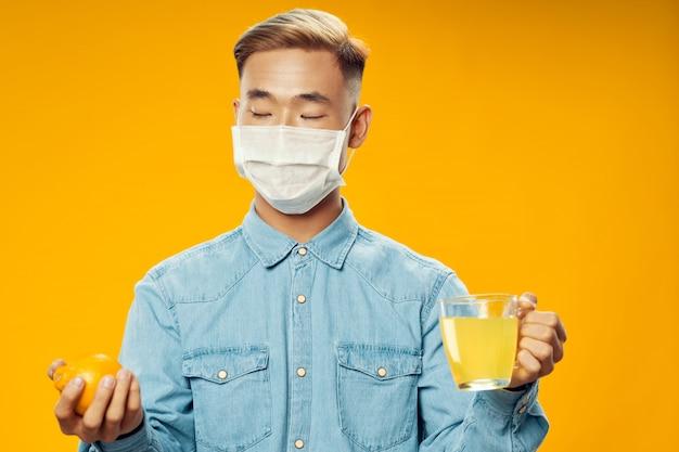 Asiatischer mann auf hellem farbhintergrund, der modell, coronavirus aufwirft