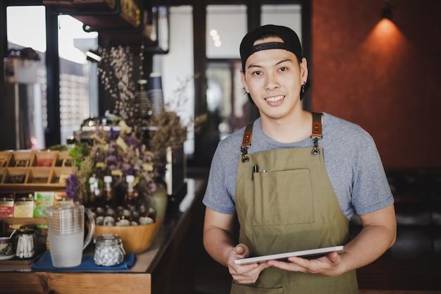 Asiatischer mann barista, der tablette für die prüfung der bestellung vom kunden auf kaffeecafé hält.