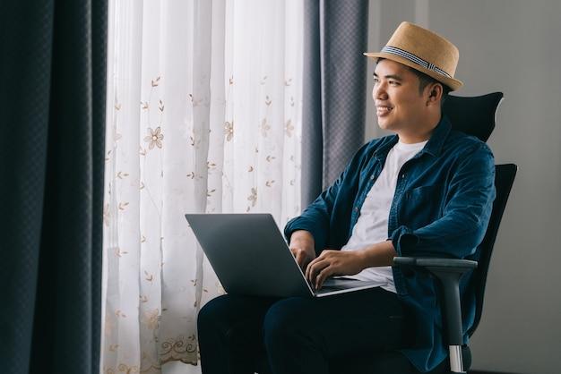 Asiatischer mann benutzt seinen laptop, um online am fenster zu arbeiten, konzeptarbeit von zu hause aus