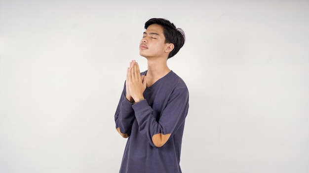 Asiatischer mann bettelt um hoffnung isoliert auf weißem hintergrund