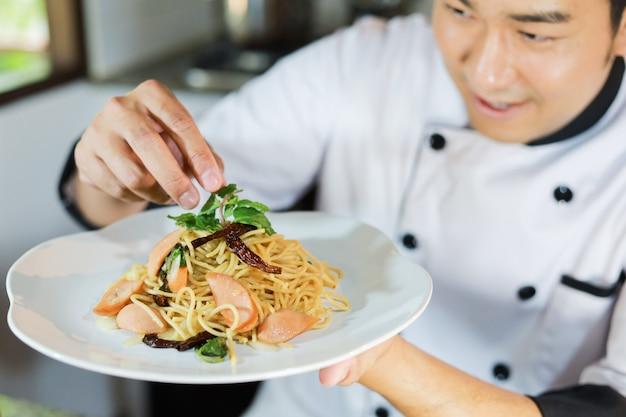 Asiatischer mann-chef, der lebensmittel im restaurant kocht