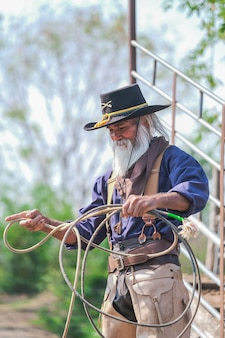 Asiatischer mann-cowboy fängt ein kalb, um in einer ranch gebrandmarkt zu werden