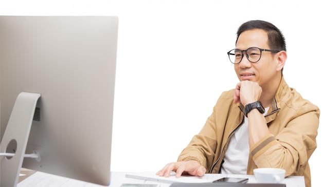 Asiatischer mann denkt und benutzt einen laptop, um im internet mit kunden zu kommunizieren