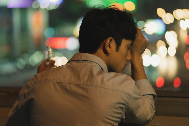 Asiatischer mann, der am abend raucht und trinkt