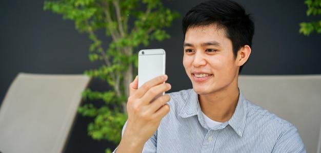 Asiatischer mann, der am garten im freien hält smartphone zum aufpassen von multimedia im internet stillsteht und mit befriedigendem gefühl lächelt