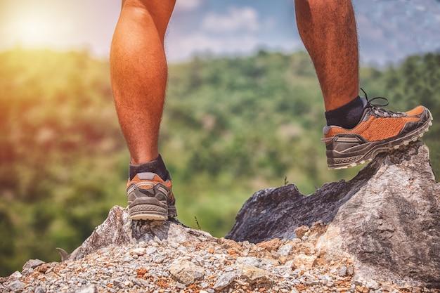 Asiatischer mann, der am rand einer klippe hoch über den bergen steht