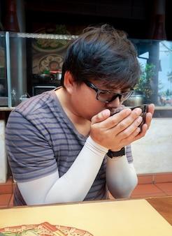 Asiatischer mann, der am tisch im restaurant suppe aus einer schwarzen schüssel hält und isst