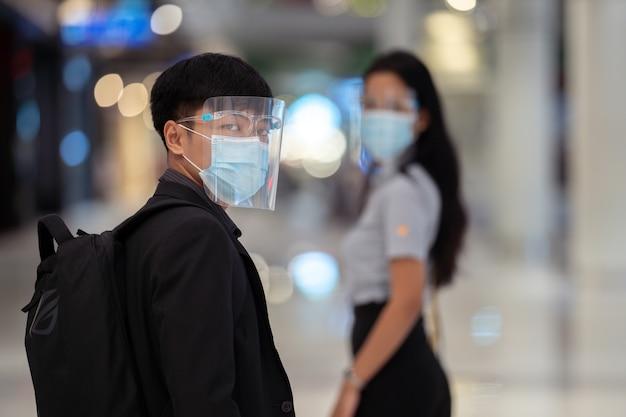 Asiatischer mann, der antivirenmasken im einkaufszentrum trägt