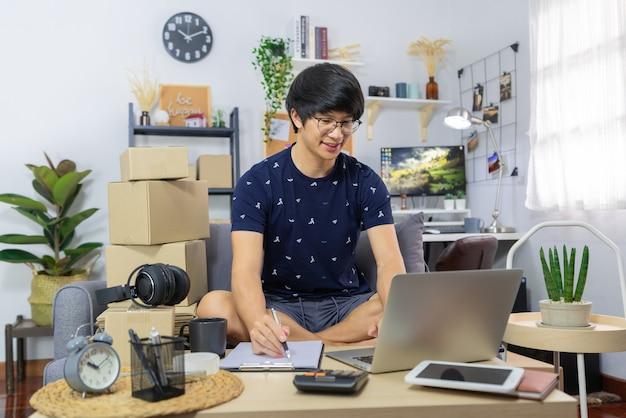 Asiatischer mann, der arbeitet, verkauft online-schreibadresse auf paket von bestellungen mit pappkarton