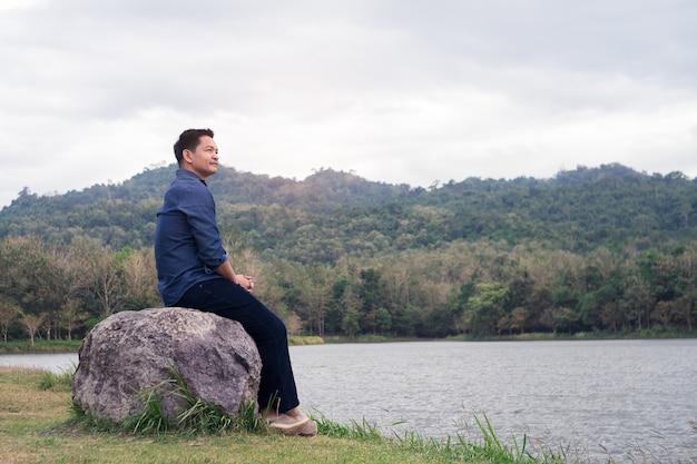 Asiatischer mann, der auf dem stein an der grünen natur mit glücklichem und komfort sitzt.