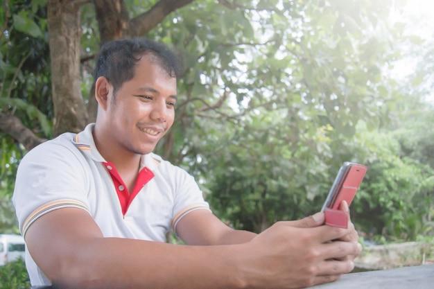 Asiatischer mann, der auf dem tisch handy im park verwendet er schauen happymoment. konzept von entspannen sich die leute, die tragbare geräte bearbeiten.