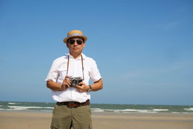 Asiatischer mann, der auf der sommerzeit des strandes und des blauen himmels mit weinlesekamera glücklich sich fühlt