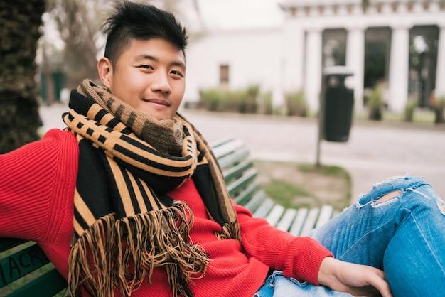 Asiatischer mann, der auf einer bank im park sitzt.