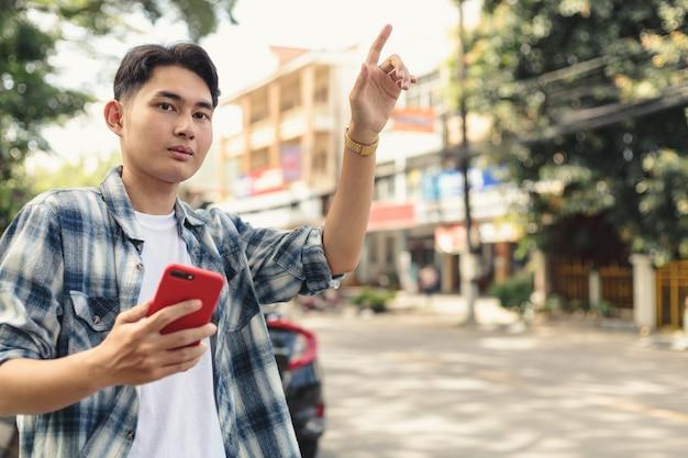 Asiatischer mann, der auf uber taxi wartet