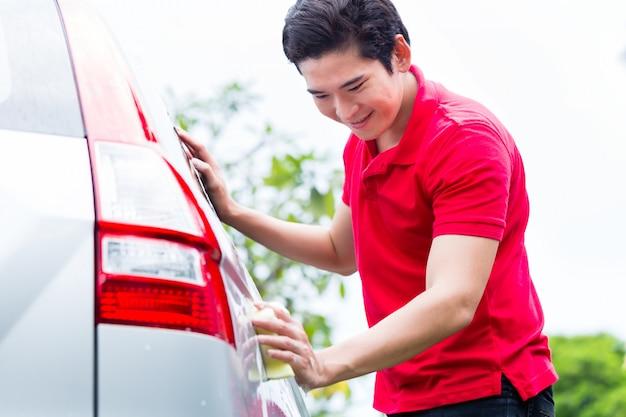 Asiatischer mann, der auto mit schwamm säubert und wäscht
