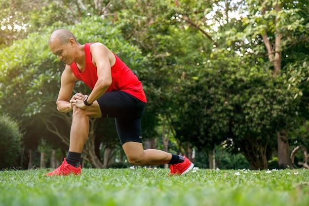 Asiatischer mann, der bein im park nach dem laufen am morgen ausdehnt.