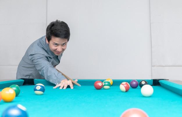 Asiatischer mann, der billards, sport und erholung spielt