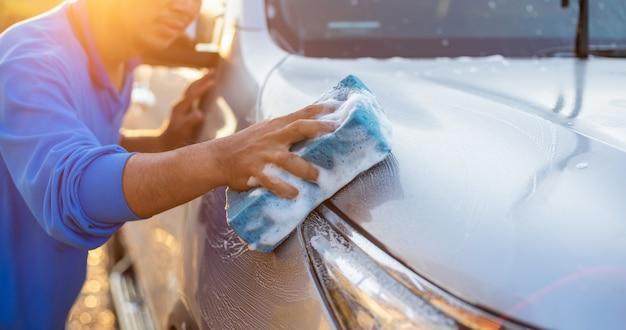Asiatischer mann, der blauen schwamm mit seife verwendet, um das auto an im freien in der sonnenuntergangzeit zu waschen