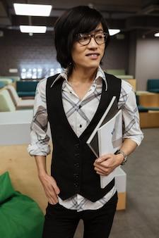 Asiatischer mann, der brille in jacke und hemd trägt